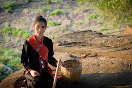 Phu Thai (Thai Language) girl stand on the rocks near the river.
