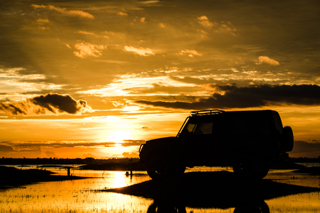 Silhouette car off road on the river over sunset background.
