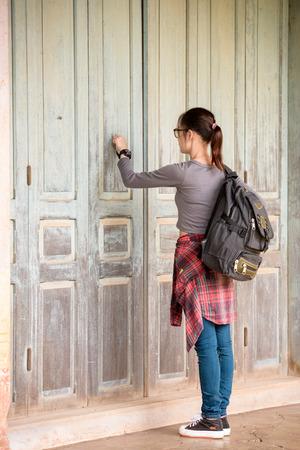 Fille asiatique hipster frappe à sa porte. Banque d'images
