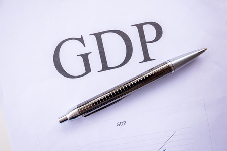 GDP words on the paper with a pen. Stock Photo