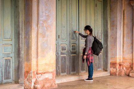 Hipster Aziatisch meisje klopt op haar deur.
