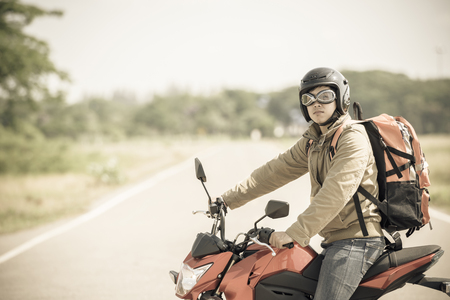Backpackers or travelers are traveling by motorbike.