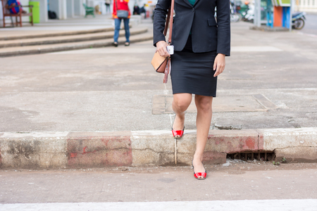 Business woman walking across the crosswalk