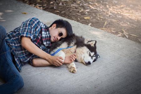 Siberian husky dog sleep on a cement floor with the owner.