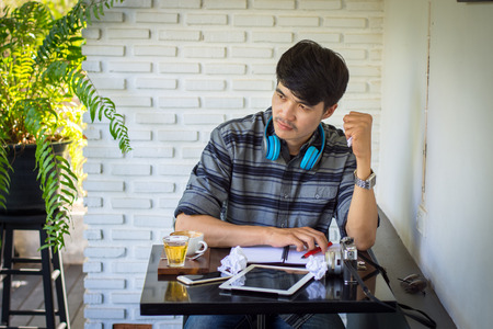 Young man wearing a headset sitting and reading the paper reported in a coffee shop. Unhappy.