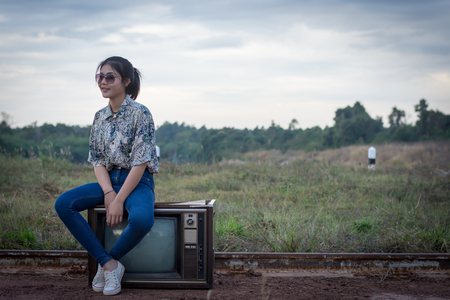 Young woman enjoying sitting on an old television.
