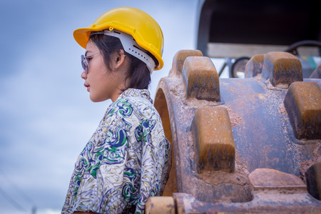 Woman engineer in road construction and rollers have a background.