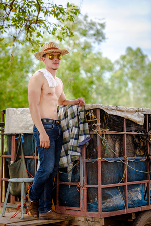Asian farmer wearing jeans, standing near the container Imagens