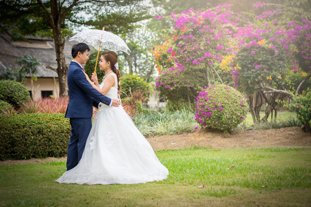 Beautiful Young wedding couple with white umbrellas holding hands in the green park. Stock Photo