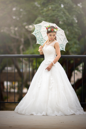 Young girl in a bridal gown holding a white umbrella on a steel bridge.