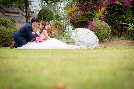 Beautiful Young wedding couple with white umbrellas sitting on a green lawn. Man gave flowers to young woman.