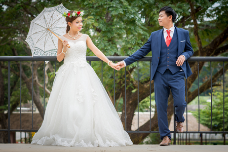 Couple standing holding hands while bride holding white umbrella.