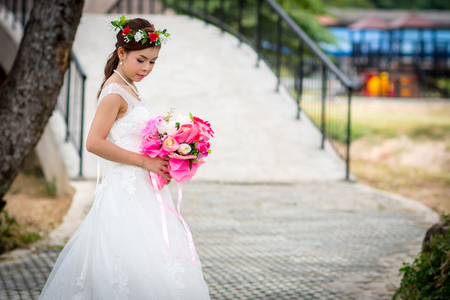 Woman wearing a wedding dress and with holding a bouquet of flowers standing on cement floor.  Over Bridge in the background. Foto de archivo