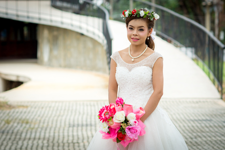 Woman wearing a wedding dress and with holding a bouquet of flowers standing on cement floor.  Over Bridge in the background. Stock Photo