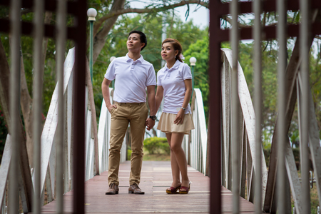 Young men and young women Couple together standing on the bridge looking sky. Both were wearing white shirts.