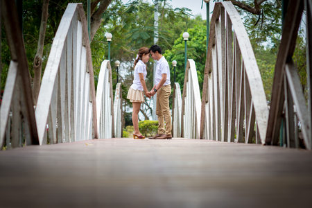 Young men and young women Couple together standing on the bridge. Both were wearing white shirts.