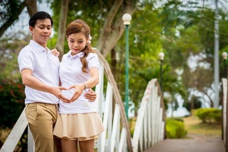 Beautiful Young couple with white coats standing on the bridge. And made a heart shape. Stock Photo