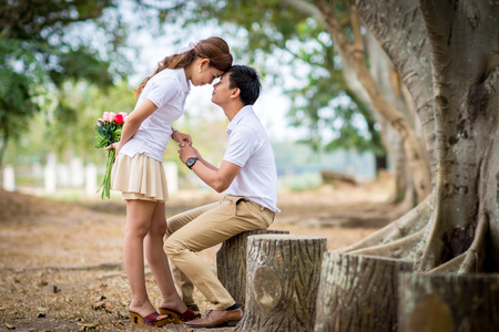Beautiful Young couple with white coats sitting in the green park. Man send a bouquet of flowers to a woman. Stock Photo