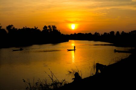 fisherman silhouette at moonnoi in thailand Stock Photo