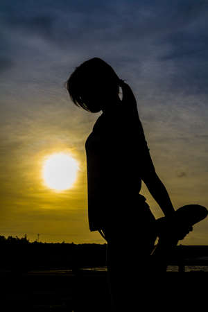 Silhouette of Woman Practicing Yoga  Warrior Pose  photo