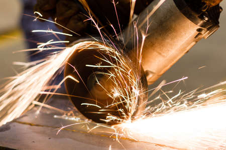 Worker cutting metal with many sharp sparks photo