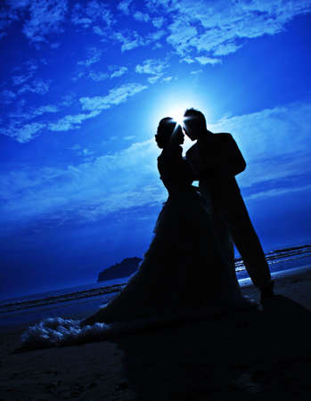 romantic young couple sunset silhouette on beach. honeymoon photo