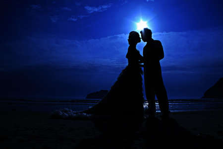 siluetas de enamorados: romántica puesta de sol silueta joven pareja en la playa. luna de miel Foto de archivo