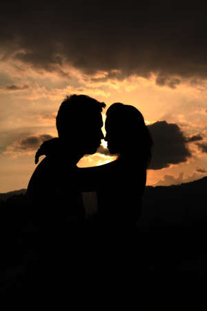 Two young lovers standing on sunset background  Zdjęcie Seryjne