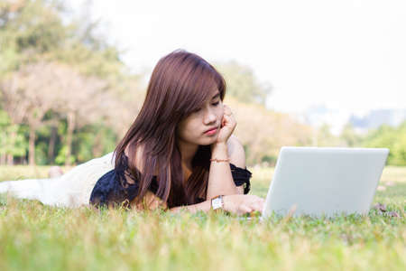 Young pretty woman with laptop lying in a park photo