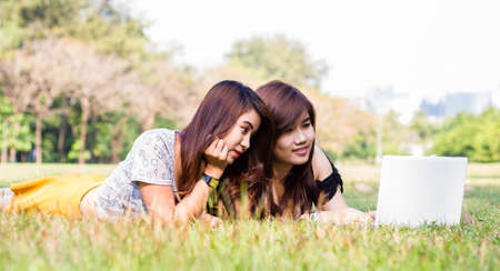 Young pretty woman with laptop lying in a park Stock Photo - 17425046