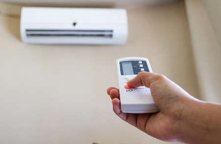 hands in the air: Closeup view about using some appliance such as air condition