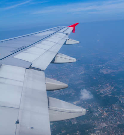 airfoil: Aircraft wing on during flying above ground Stock Photo