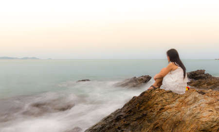 lonely person: A sad and depressed woman sitting by the ocean deep in thought.