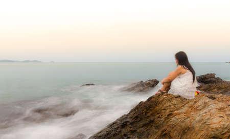 Een verdrietig en depressief vrouw zitten door de oceaan diep in gedachten.