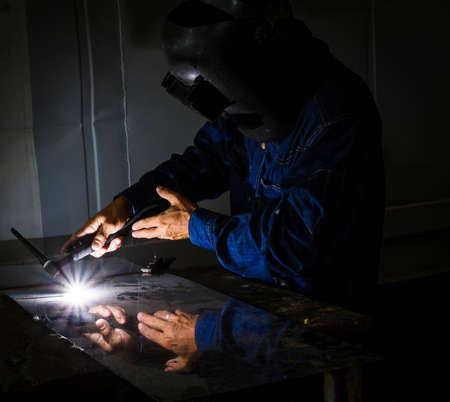 Industrial welder welding on steel in factory photo