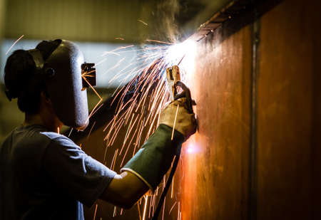 making a fire: worker with protective mask welding metal and sparks  Stock Photo