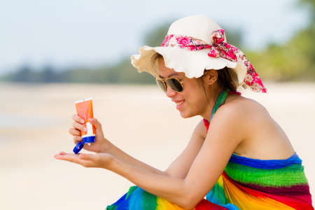 Sunscreen woman. Girl putting sun block on beach holding Stock Photo