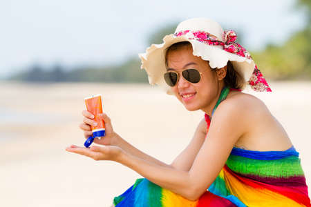 Sunscreen woman  Girl sun block on beach holding