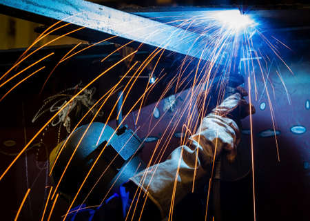 Worker with protective mask welding metal and sparks photo