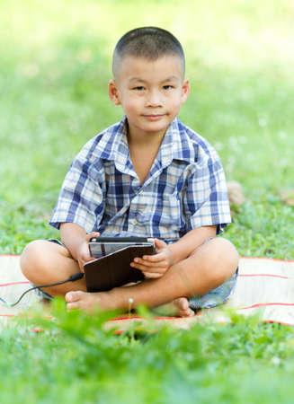 Boy holding tablet PC in garden Stock Photo - 20615705