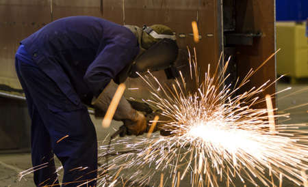 welding worker: Electric wheel grinding on steel structure in factory  Stock Photo