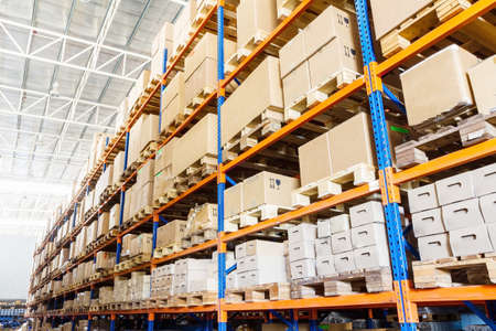 Rows of shelves with boxes in modern warehouse photo