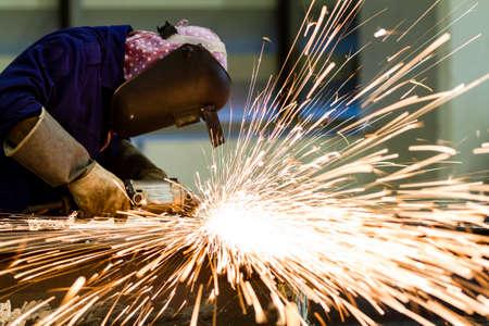 Electric wheel grinding on steel structure in factory  Reklamní fotografie