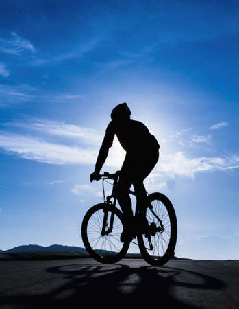 Silhouette of the cyclist riding photo