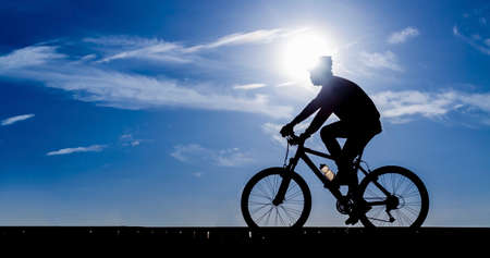 bike trail: Silhouette of the cyclist riding a road bike Stock Photo
