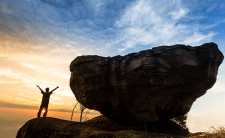 Man on top of mountain with big rock photo