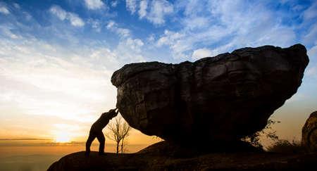 pushing: Man achter een rotsblok op een rots
