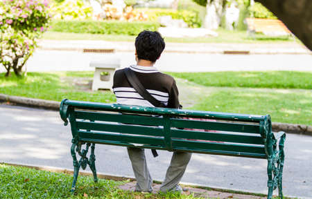 sitting on a bench: Man sitting alone on park Stock Photo