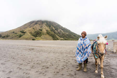 JAVA,INDONESIA - FEB 16 Indonesia man with the horse for tourist rent at Mount Bromo on Febuary 16, 2014 in Java , Indonesia Mt  Bromo is an active volcano and part of the Tengger massif, in East Java