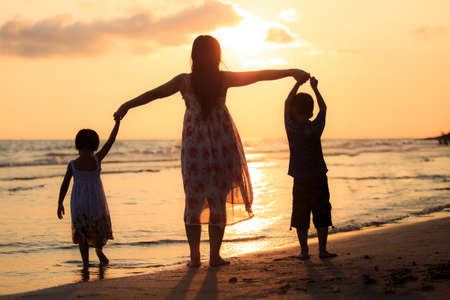 Mother with her daughter and son on the beach photo